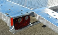 Trailer with alloy tread floor and steel ramp located to load